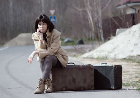 incertitude: brunette woman waiting for sitting on a suitcase