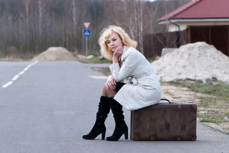 incertitude: blond woman waits sitting on a suitcase Stock Photo