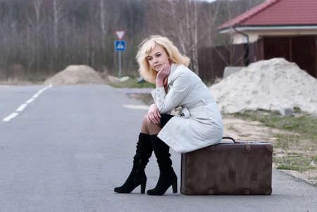 suspenso: mujer rubia Esperas sienta en una maleta Foto de archivo