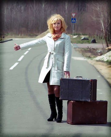 blonde girl standing on the road with a suitcase and hitchhiking shows