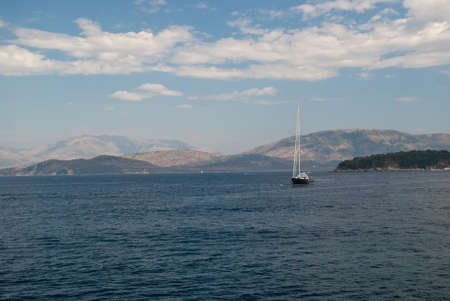 beautiful seascape sailing boat on a background of mountains