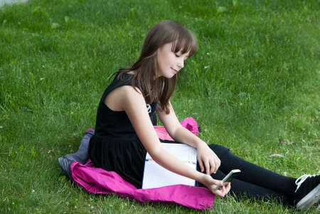 teenager girl sitting on the grass and makes selfie mobile phone