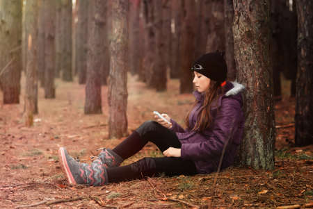 teenager girl sits in the autumn forest with a mobile phone Stock Photo
