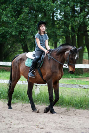 Teenage girl riding a horse Stock Photo