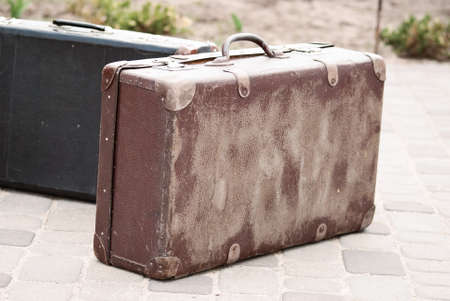 portmanteau: old brown retro suitcase close-up on the road
