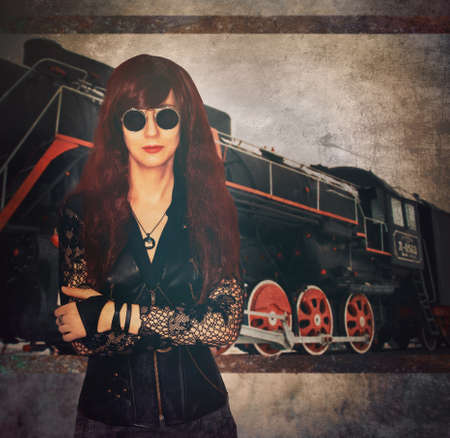 girl in the steampunk style stands on the background of the locomotive Stock Photo