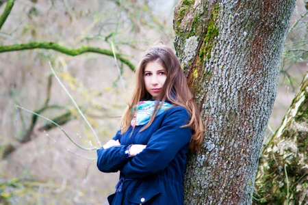 The girl is standing near the tree Stock Photo