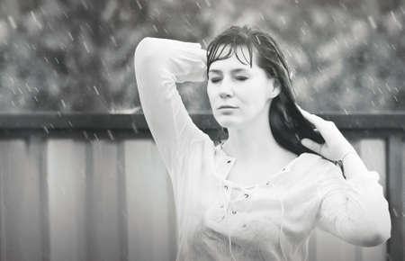 女性は、目を閉じながら雨の中で立っています。