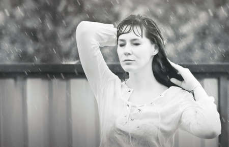 Een vrouw staat in de regen met haar ogen dicht
