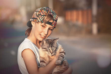 Girl teenager holding a gray cat