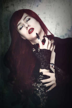 A woman is a vampire with red hair and black claws.