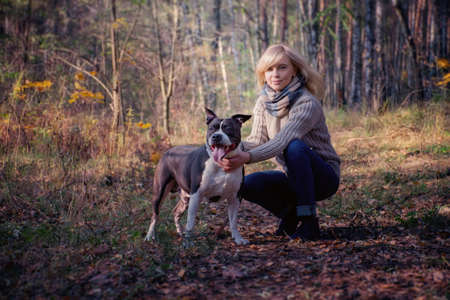 A blonde woman is walking with a dog in the forest