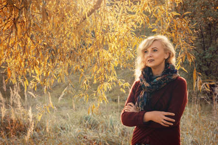 middle-aged woman walking in the autumn in the forest Stock Photo
