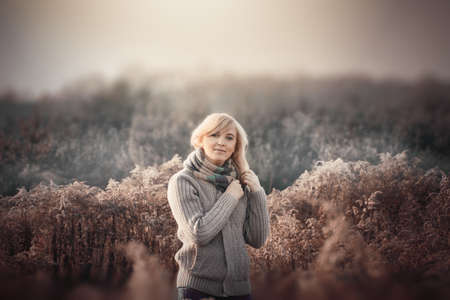 A woman is standing in a field in the fall in November. Stock Photo