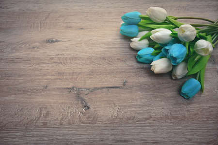 bouquet of multicolored tulips on a wooden background and with an empty place for an inscription