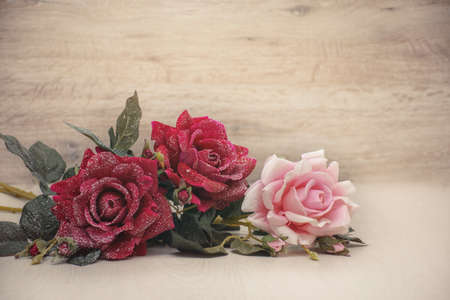 Bouquet of three snow roses on a wooden background with space for congratulations