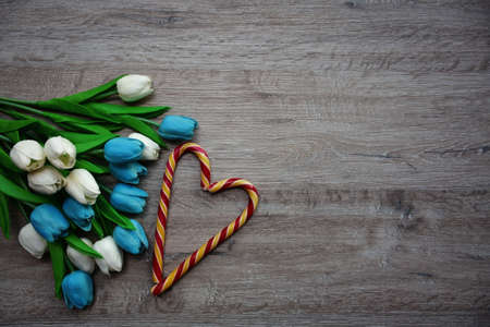 heart made of chocolates and a bouquet of tulips on a wooden background