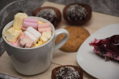 White cup with marshmallow and different sweets on a wooden tray
