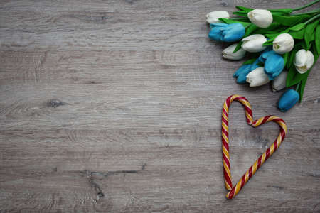 heart made of sugar candies and a bouquet of tulips on a wooden background