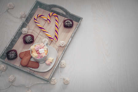 many different sweets on a tray and free space for an inscription on a wooden background