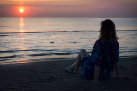 a woman is sitting on the beach and looking at sunrise in the sea