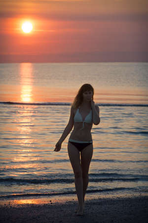 a woman walks in the morning by the sea on the background of dawn Stock Photo