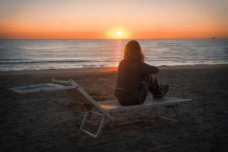 girl meets sunrise on the sea beach