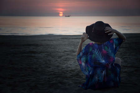 woman in a hat sits on the beach and looks at the sunrise at the sea