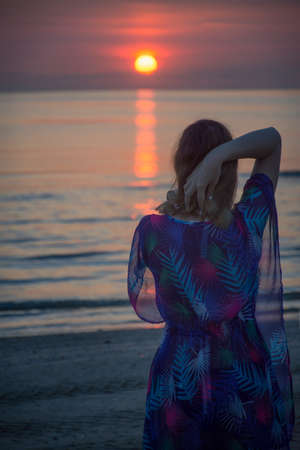 a woman is standing on the beach and looking at the sunrise in the sea Stock Photo
