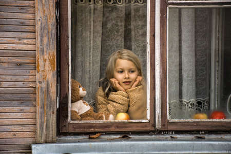 the girl is sitting in the house by the window and looks at the street