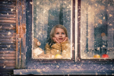 girl looks out the window at the falling snow Stock Photo