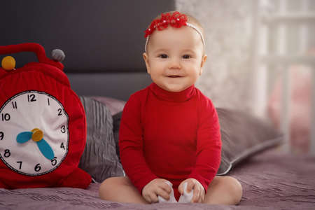 large portrait little beauty baby in red on a dark background