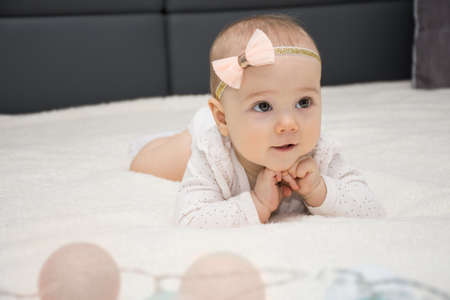 portrait of a little naughty cute babe is lying on her tummy and smiling