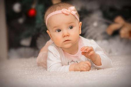 close-up baby girl lying under a christmas tree Фото со стока