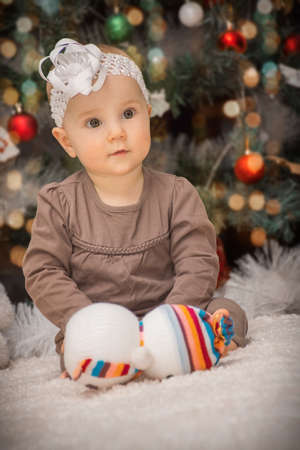 portrait little baby is lying on the tummy under the Christmas tree against the background of soft toys Фото со стока