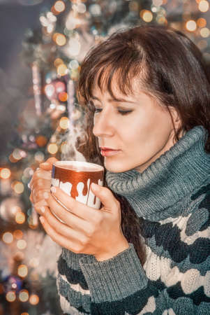 girl enjoys the smell of a hot drink in the Christmas background Фото со стока
