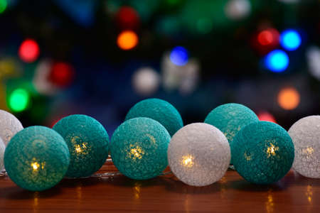 electric garland on a wooden background on bokeh background of Christmas tree lights Фото со стока