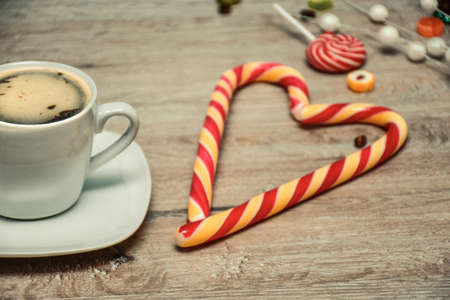 cup of coffee and candies on wooden background