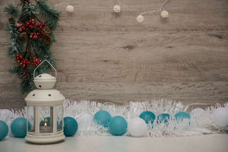 textured wooden board as a background for text space, decorated with Christmas lights and a garland, and pine cone Фото со стока