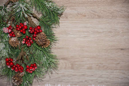 textured wooden board as a background for text space, decorated with Christmas  pine branch and cones