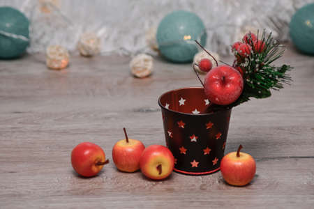 red apples ranetki close-up and Christmas decor on a wooden background