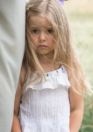 very sad little girl hid behind her mom