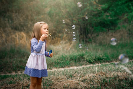 little girl inflates soap bubbles in the summer on the street