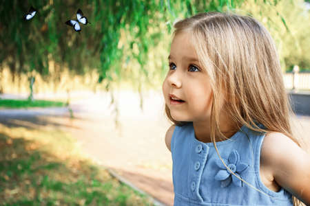 little girl looks surprised at blue butterflies in summer