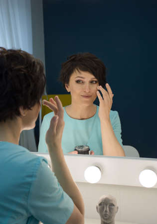 reflection in the mirror of a woman who applies cream on her face