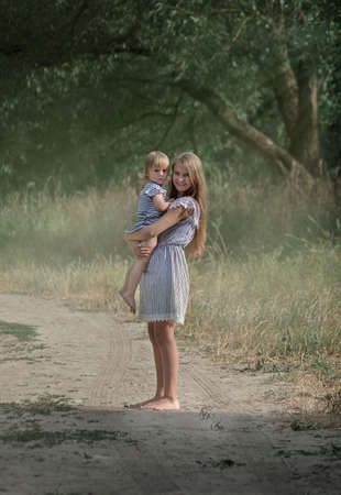 older sister holds little sister in her arms Stock Photo
