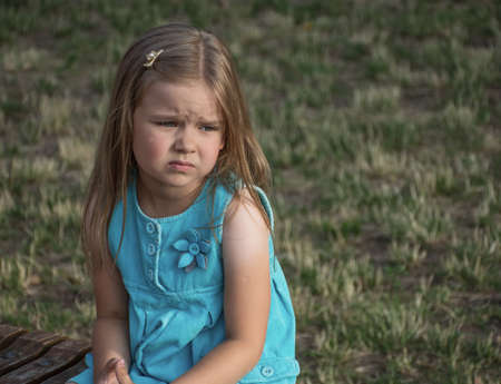 very sad little girl in a blue dress on the street