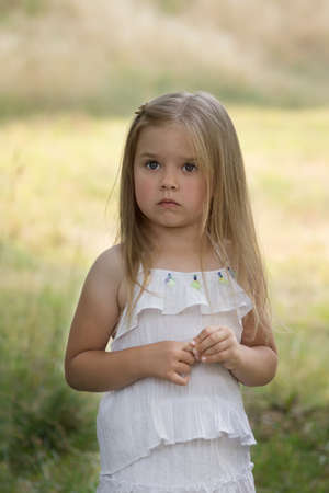 sad little girl in a white dress on summer yellow sunny backgroundt