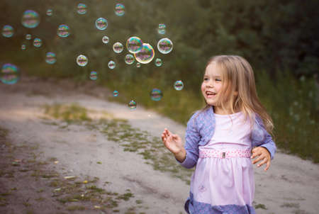 Little girl laughs playing with soap bubbles on the street in summer.