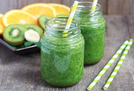 licuado de platano: Batido verde saludable de espinacas, kiwi, plátanos y naranjas en un frasco con pajas amarillas en una mesa de madera, enfoque selectivo